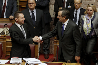 Greece's Prime Minister Samaras shakes hands with Finance Minister Stournaras after a vote at the parliament in Athens