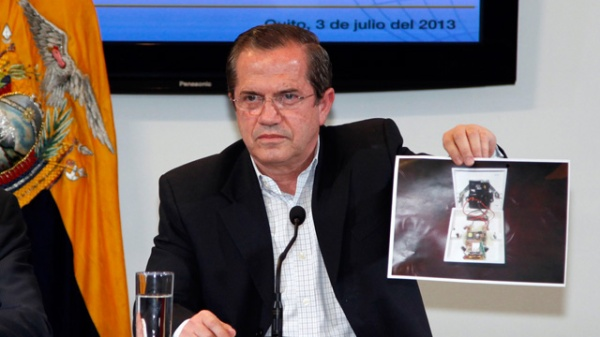 Ecuador's foreign minister holds a picture of a hidden microphone