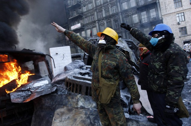 Anti-government protesters gesture at a barricade at the site of clashes with riot police in Kiev